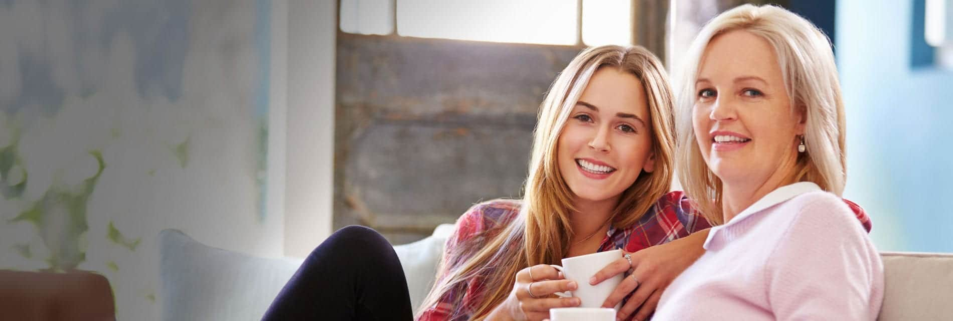 two smiling women with coffee cups