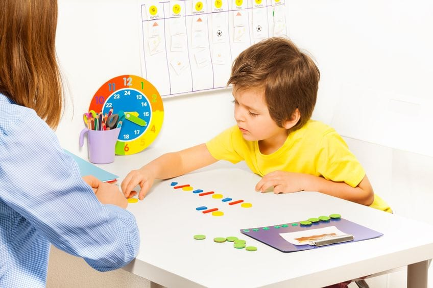 young boy organizing shapes with his mother