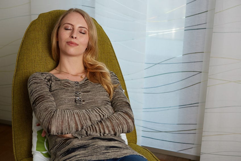 woman on chair sleeping and smiling