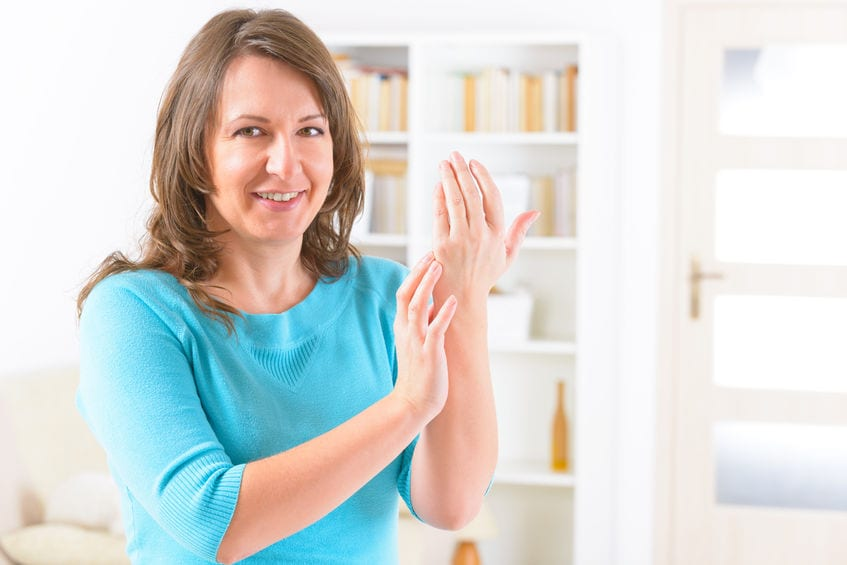 smiling women touching the side of her hand - EFT/Tapping example