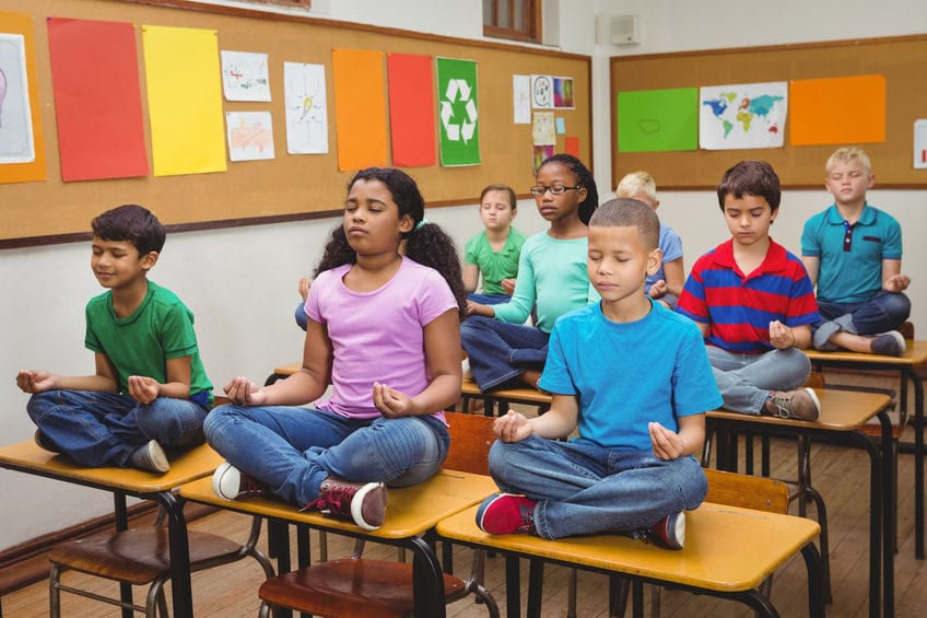 children in schoolroom sitting on desks - Meditation, Mindfulness Training, and Guided Vizualizations