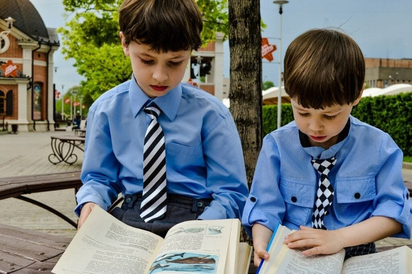 two young schoolboys reading outside