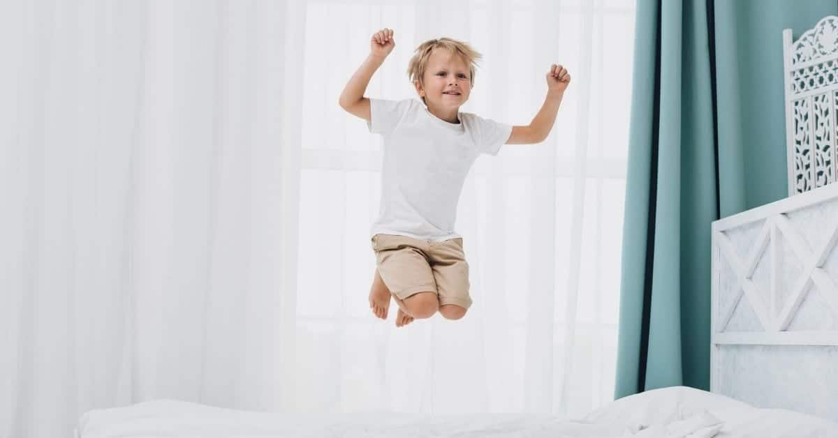 extroverted child jumping on bed