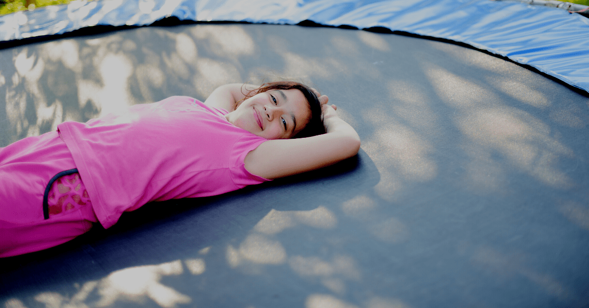Child laying on a trampoline